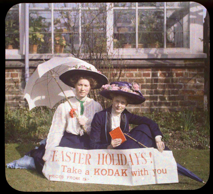 Two_women_holding_a_sign_that_readsEaster_Holidays!_Take_a_Kodak_with_you_Prices_from_5-_(3333256161)